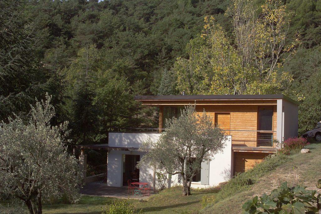 Photographie de l'extérieur de la a surélévation en ossature bois avec son bardage bois et sa toiture terrasse