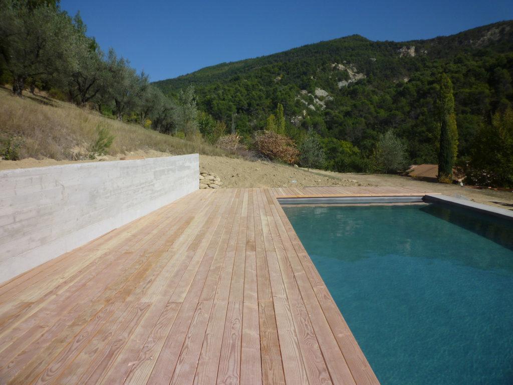 Photographie de la plage de la piscine en bois avec mur de soutènement en béton planche et vue sur la végétation