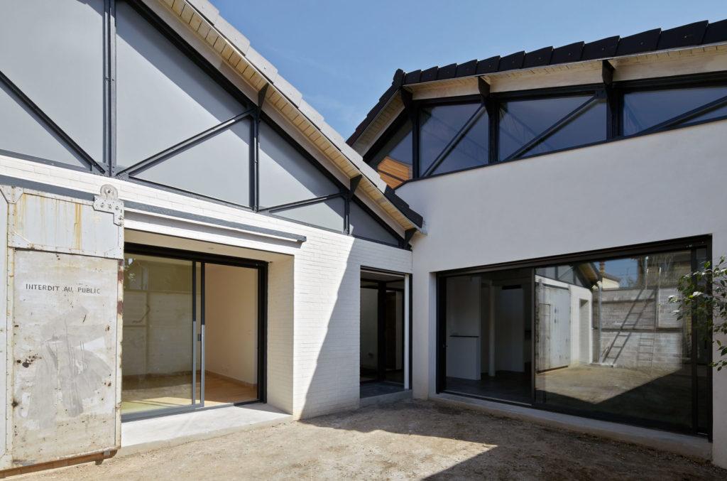 Photographie des façades pignons dont les charpentes métalliques sont apparentes. Le caractère industriel des bâtiments d'origine est préservé.
