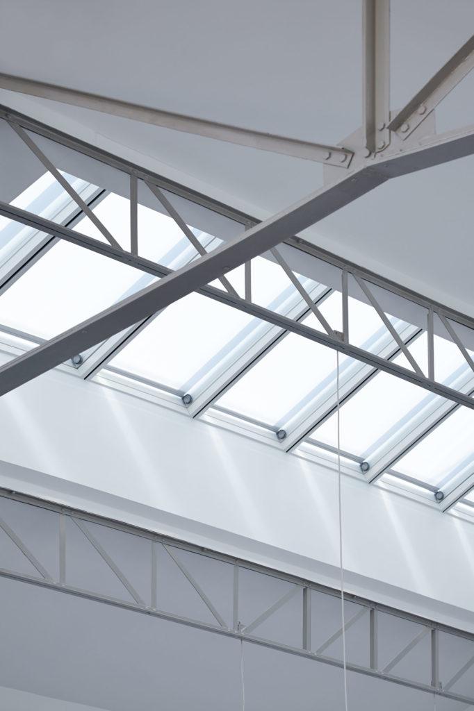 Photographie en gros plan sur la charpente métallique et l'ouverture en toiture apportant de la lumière naturelle à l'intérieur du loft.