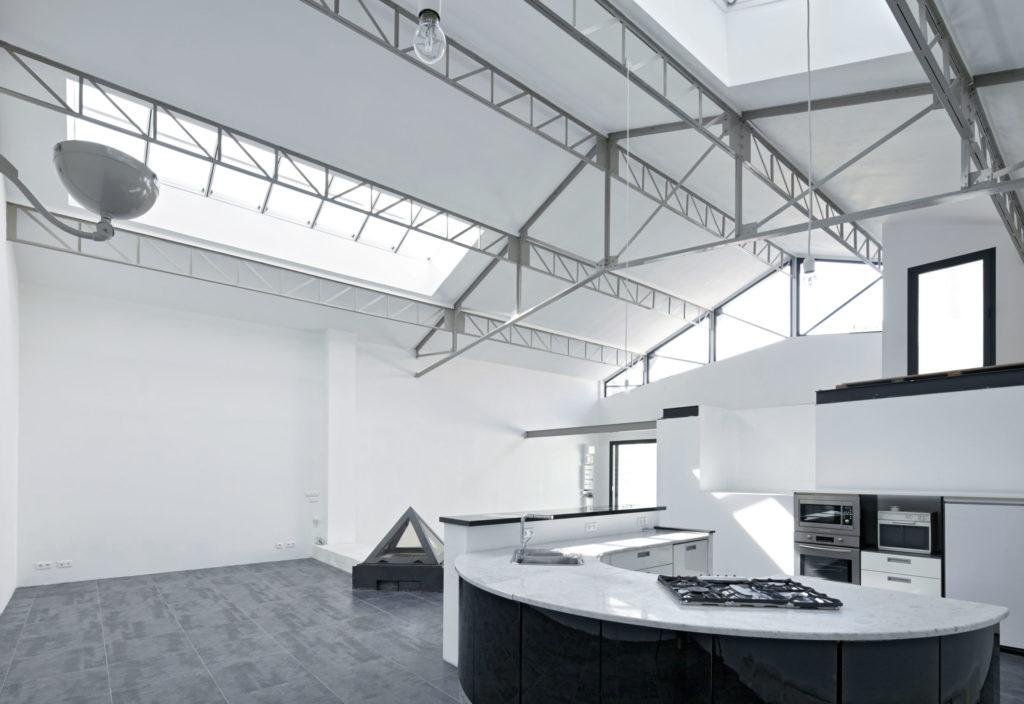 Photographie de la pièce de vie où la charpente métallique est apparente. Les ouvertures en toiture et sur les pignons apportent de la lumière naturelle à l'intérieur du loft.