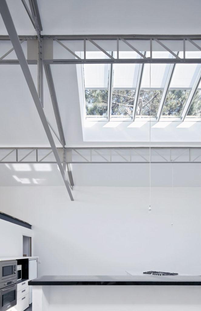 Photographie de la cuisine où la charpente métallique est apparente. L'ouverture en toiture apporte de la lumière naturelle à l'intérieur du loft.