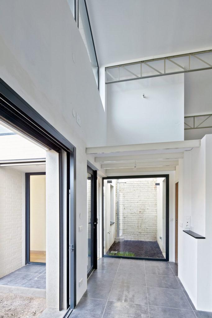 Photographie à l'entrée du logement avec vue sur le patio qui apporte de la lumière naturelle par le biais d'une grande baie vitrée.