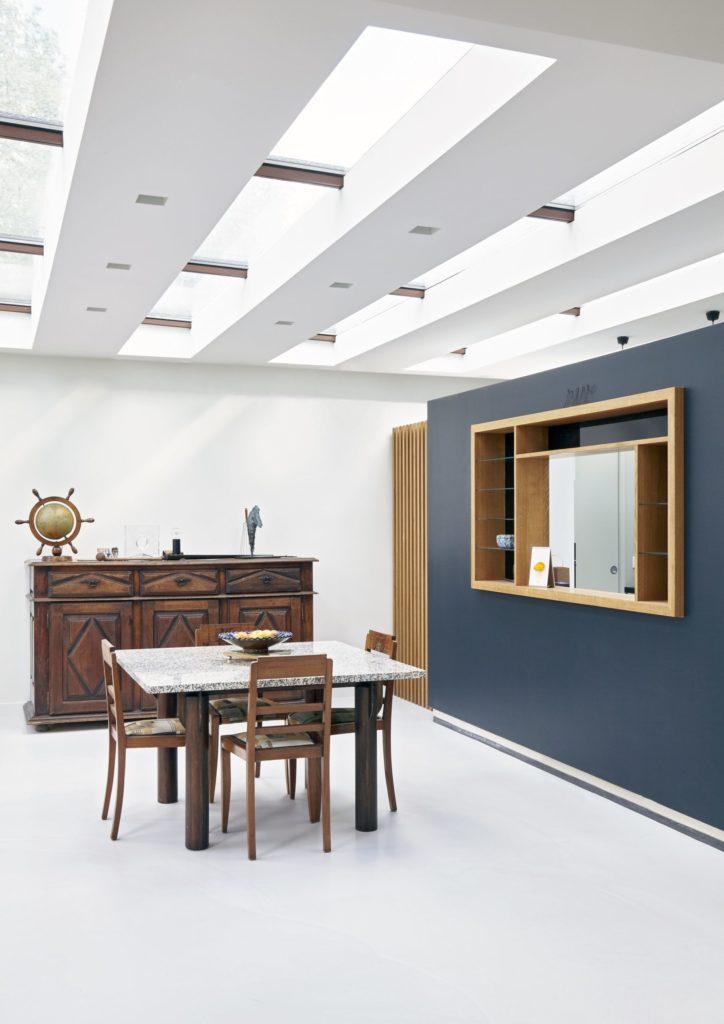 Photographie du séjour lumineux grâce aux ouvertures en toiture. Les murs et le sol sont blancs sauf le mur de la cuisine en îlot qui est bleu. L'ouverture de l'îlot sur le séjour est soulignée par un cadre en bois.