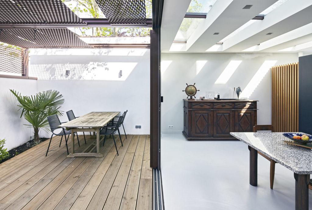 Photographie prise au niveau de la baie coulissante du séjour, qui se situe dans l'extension Sud de la maison, ouverte sur le jardin d'hiver et la terrasse en bois.