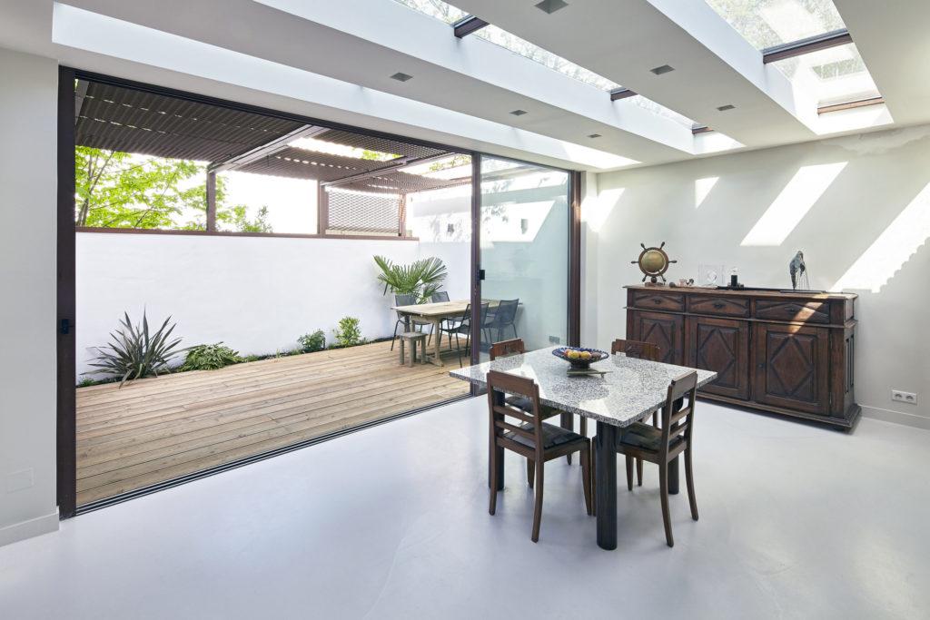 Photographie du séjour lumineux grâce aux ouvertures en toiture et à la grande baie vitrée donnant sur la terrasse. Les murs et le sol sont blancs, le mobilier en bois.