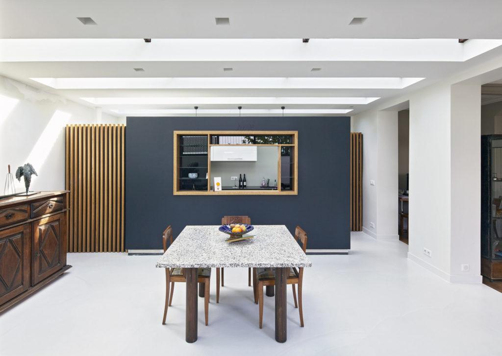Photographie du séjour blanc lumineux en premier plan et de la cuisine en îlot en second plan. Un cadre en bois souligne l'ouverture de l'îlot et contraste avec le bleu du mur.
