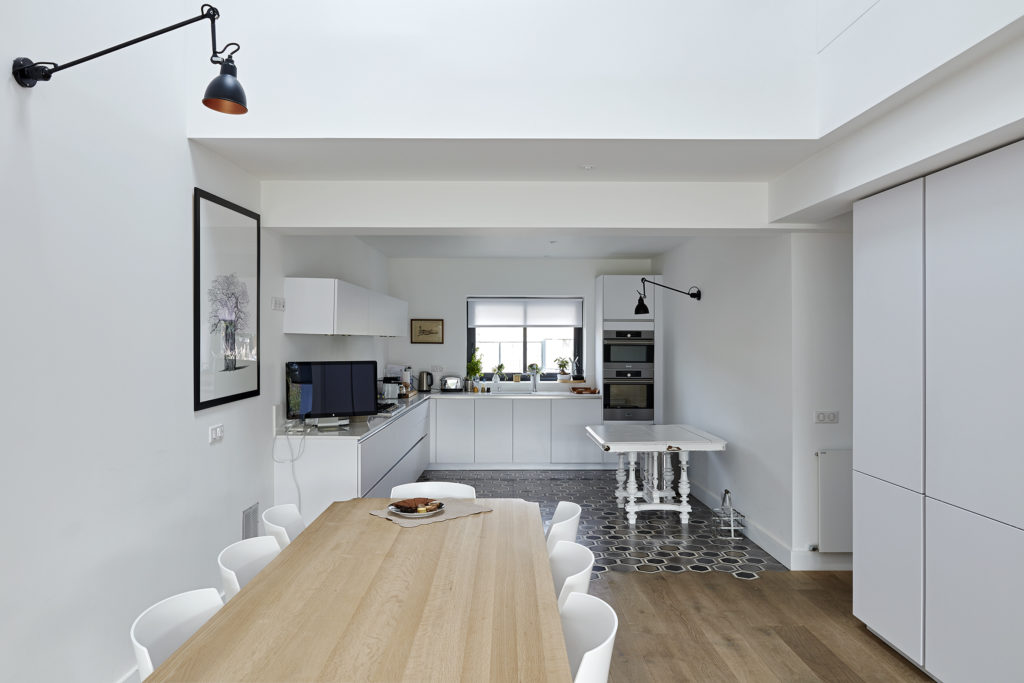 Photographie montrant au premier plan la table à manger en bois et en arrière plan la cuisine en L où les meubles sont en blanc laqué et où le sol en mosaïque vient se fondre dans le parquet bois.
