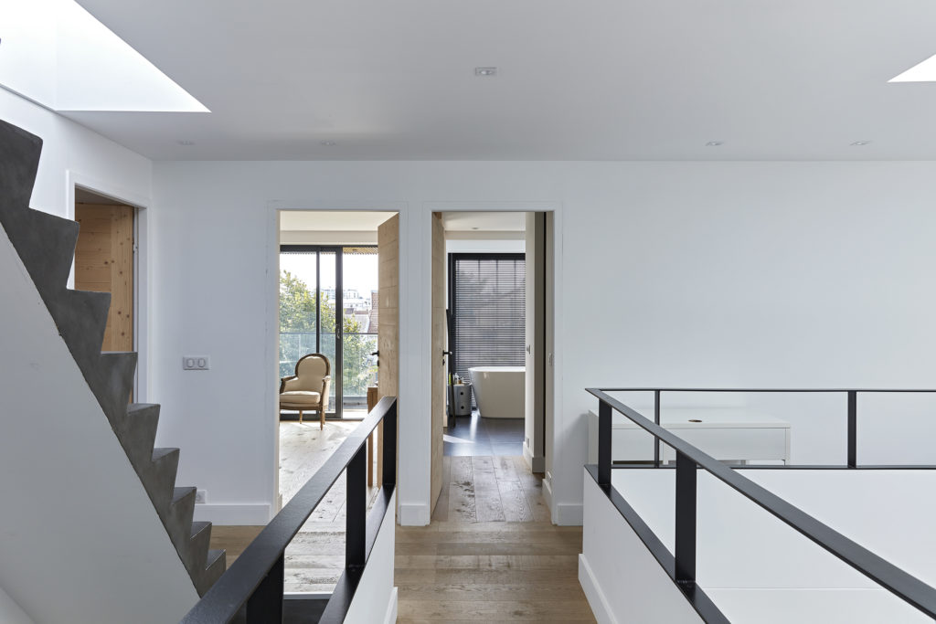 Photographie de l'étage (vue vers les chambres et salle d'eau) où les matériaux sont bruts : parquet bois, portes en bois, garde corps en acier et escalier en béton coulé sur place.