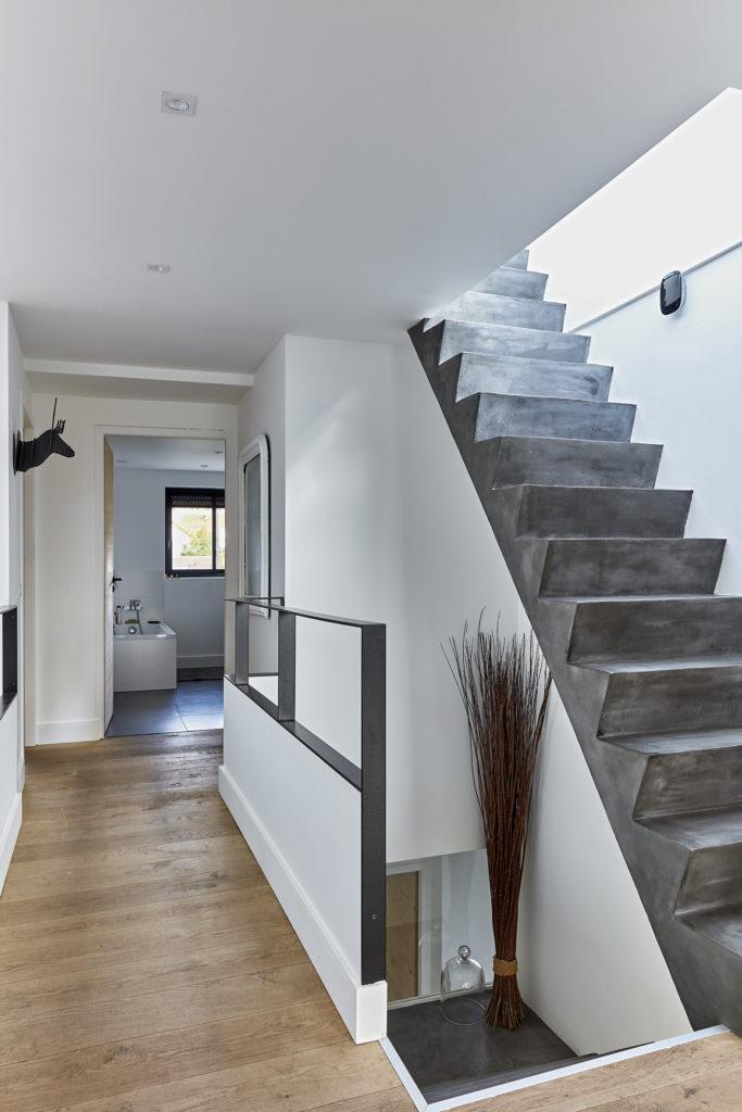 Photographie prise depuis l'étage montrant au premier plan l'escalier en béton coulé sur place, le parquet bois au sol, le grade corps acier et en arrière plan la salle d'eau à la porte en bois.