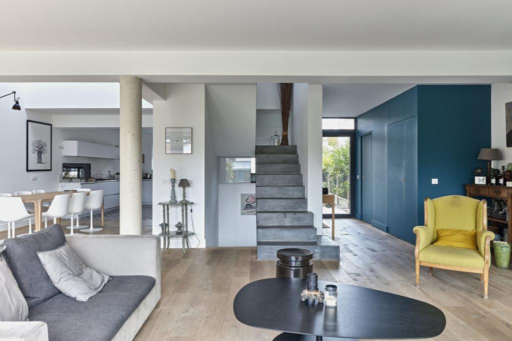 Photographie de la pièce de vie au parquet bois au sol et aux murs blancs et bleus. La vue est prise face à l'escalier béton coulé en place, la cuisine se situe sur la gauche et l'entrée sur la droite.
