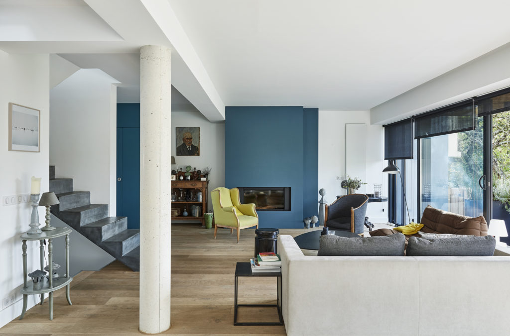 Photographie de la pièce de vie aux murs blancs et bleus, et parquet bois au sol, donnant accès au le jardin via une grande baie vitrée.