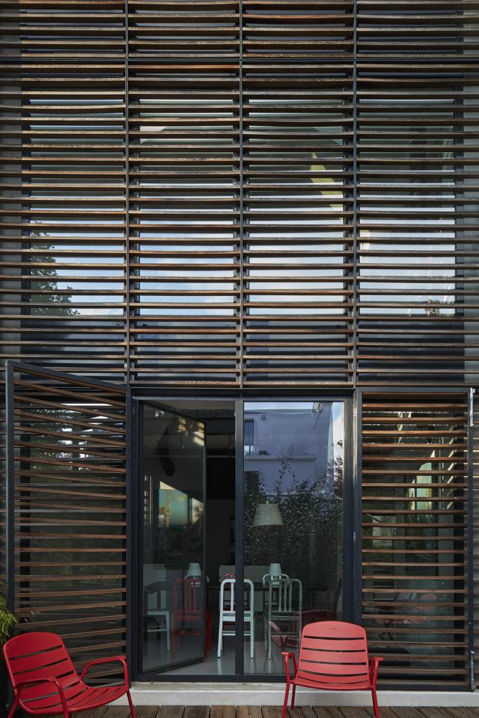 Photographie de l'accès à la terrasse avec les brises soleil en bois dans un cadre acier