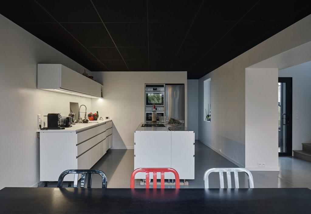 Photographie de la cuisine avec plafond noir et sol en béton