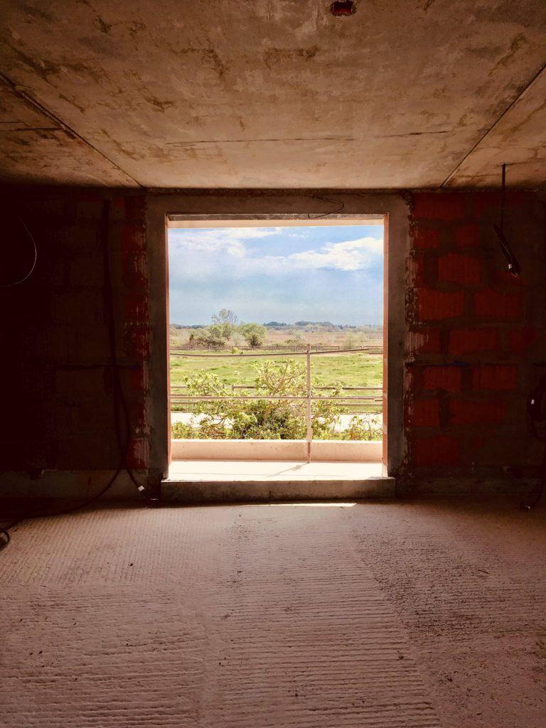Photographie montrant le cadrage sur le paysage depuis l'intérieur du bâtiment