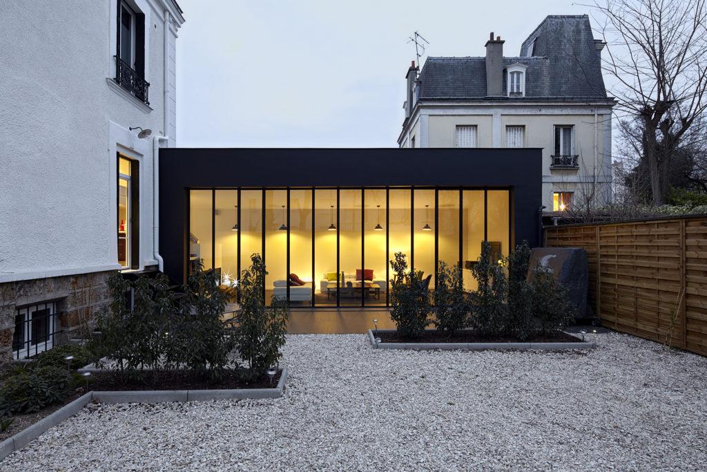Photographie de l'extension vue depuis le jardin. Les menuiseries fineline et le bardage en zinc noir ouvrent le salon vers l'extérieur.
