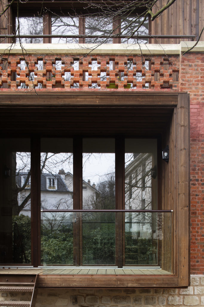 Photographie en gros plan sur la façade vitrée extérieure de l'extension bois de la maison de ville en brique.