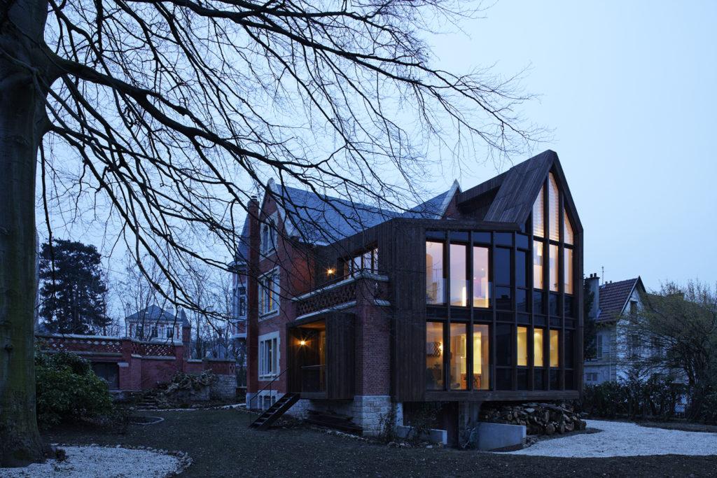 Photographie de nuit en plan moyen de l'extérieur de l'extension bois et son pignon vitré de la maison de ville, conçue en respectant son caractère patrimoniale.