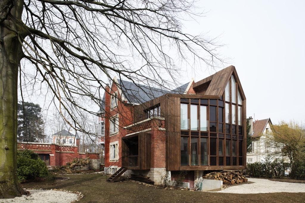 Photographie en plan moyen de l'extérieur de l'extension bois et son pignon vitré de la maison de ville, conçue en respectant son caractère patrimoniale.