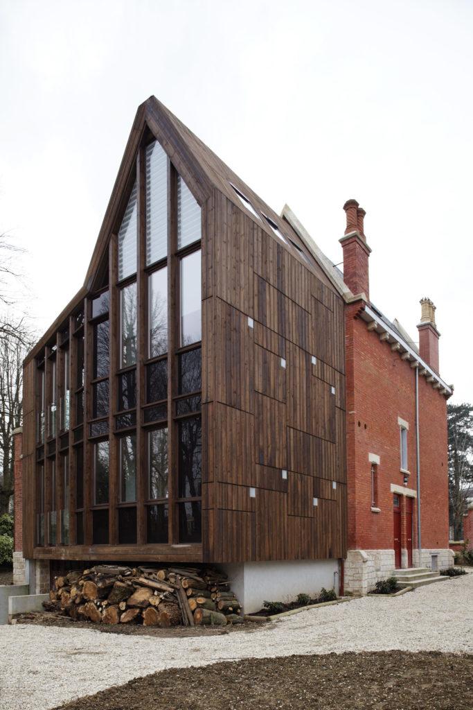 Photographie en plan proche de l'extérieur de la maison de ville avec au premier plan l'extension bois et sa façade vitrée, conçue en respectant le caractère patrimoniale de la maison existante.