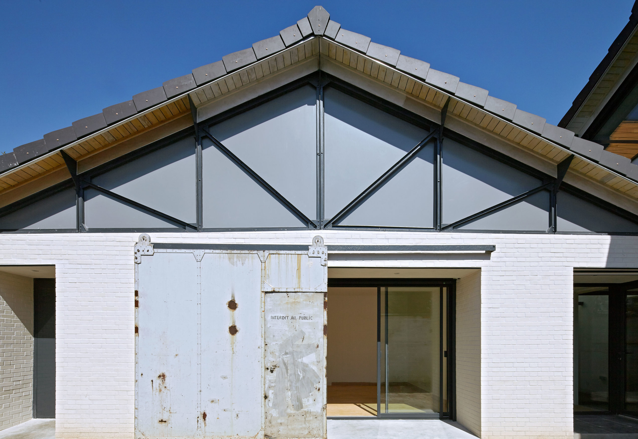 Photographie de la façade pignon en brique dont la charpente métallique est apparente. Le caractère industriel des bâtiments d'origine est préservé.