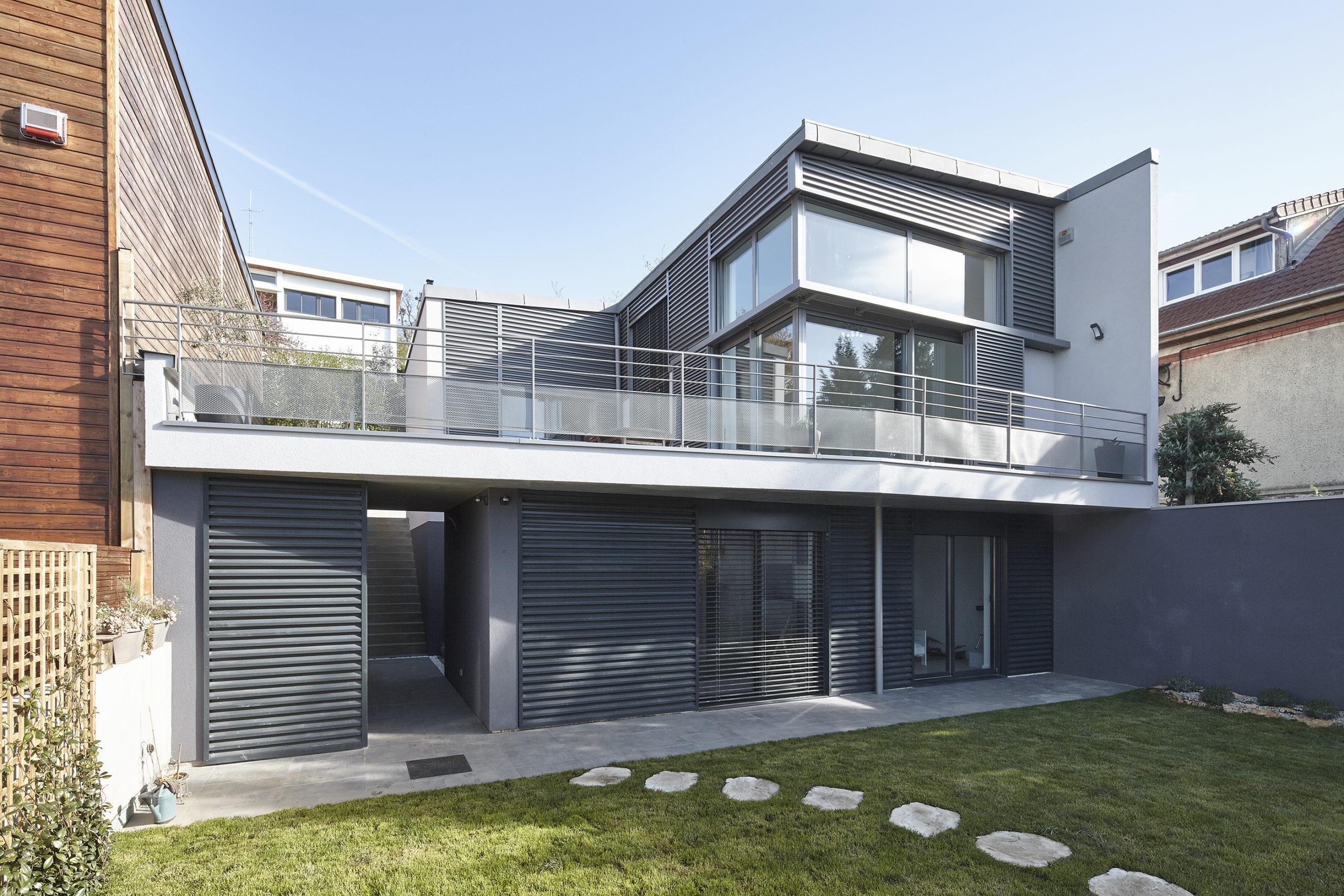 Photographie prise depuis le jardin au sud, où l'on voit le système de stores et panneaux persiennés en façade qui permet de réguler la température et l'ensoleillement sur les deux étages.