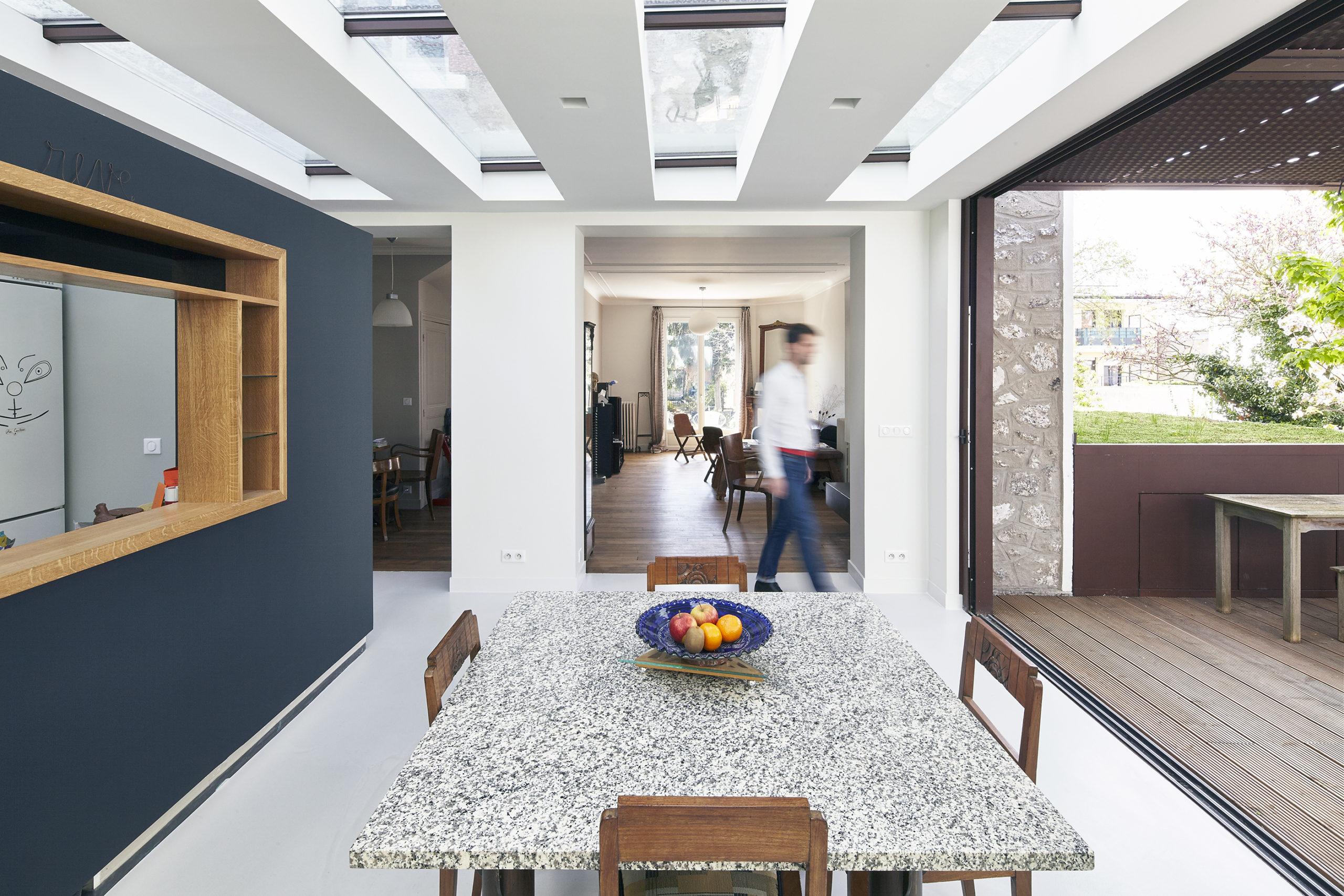 Photographie du séjour lumineux grâce aux ouvertures en toiture et à la grande baie donnant accès à la terrasse en bois. Les murs et le sol sont blancs sauf le mur de la cuisine en îlot qui est bleu. L'ouverture de l'îlot sur le séjour est soulignée par un cadre en bois.