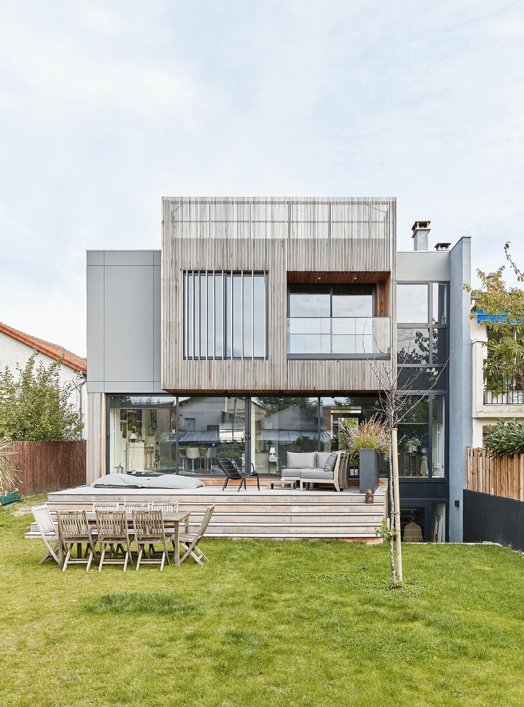 Photographie de la maison individuelle vue depuis le jardin où l'on voit la grande baie vitrée donnant sur la terrasse en bois et les revêtements de façade : le bois ajouré et les panneaux composites gris