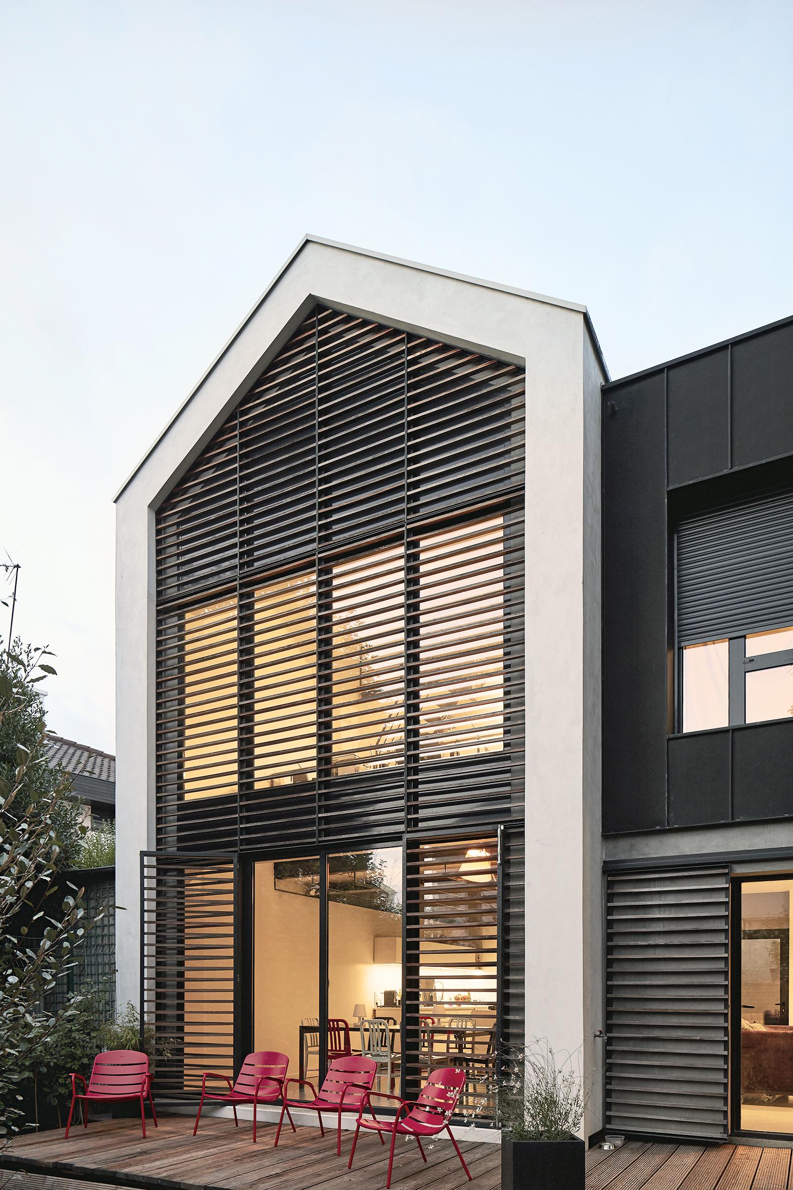 Vue de l'extension en triple hauteur avec les brises soleil en bois